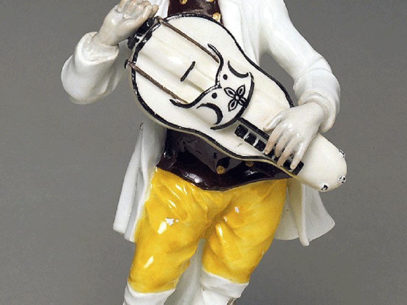 A figurine of a hurdy gurdy player