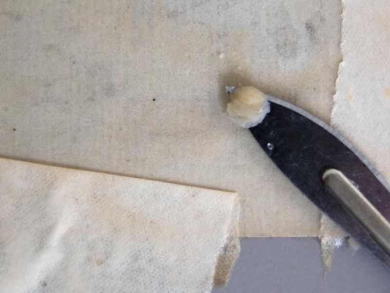 Conservator removing backing paper