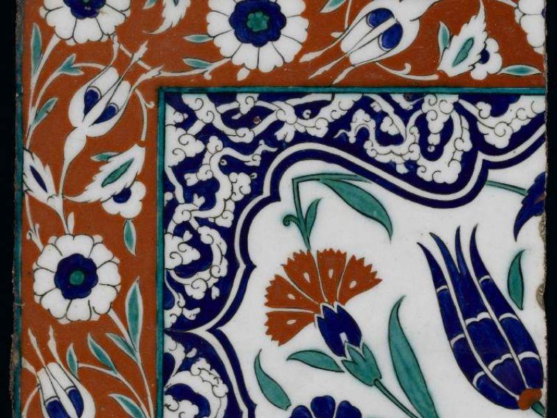 Iznik tile showing a blue tulip, red carnations and pale green serrated saz leaf.