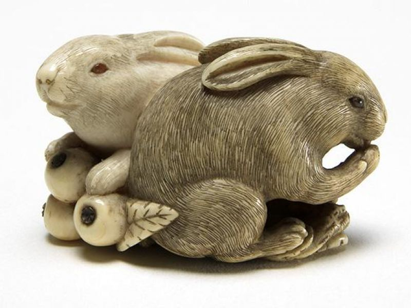 Netsuke of two rabbits eating locquats