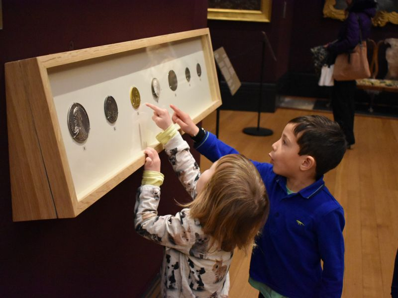 young children looking at coins in gallery 3
